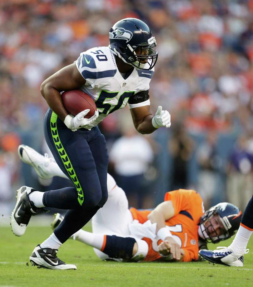 Denver Broncos quarterback Peyton Manning lies on the ground at right after Seattle Seahawks'  K.J. Wright (50) intercepted a Manning pass, in the first half. Photo: AP
