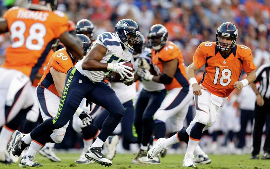 Denver Broncos quarterback Peyton Manning (18) looks on as Seattle Seahawks' K.J. Wright, center, runs with the pass Wright intercepted from him. Photo: AP