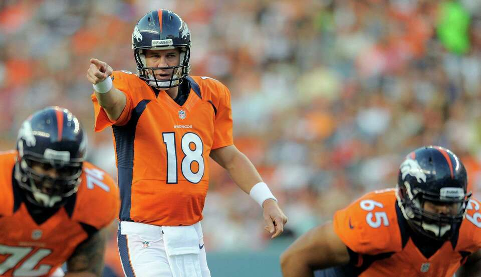 Denver Broncos quarterback Peyton Manning (18) calls to his team in the first half.