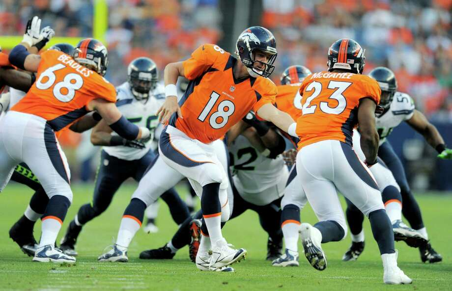 Denver Broncos quarterback Peyton Manning (18) hands off to Broncos' Willis McGahee (23) in the first half. Photo: AP