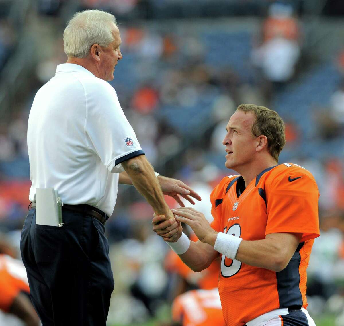 Denver Broncos head coach John Fox, left, greets quarterback Peyton Manning, right, during pregame stretching.
