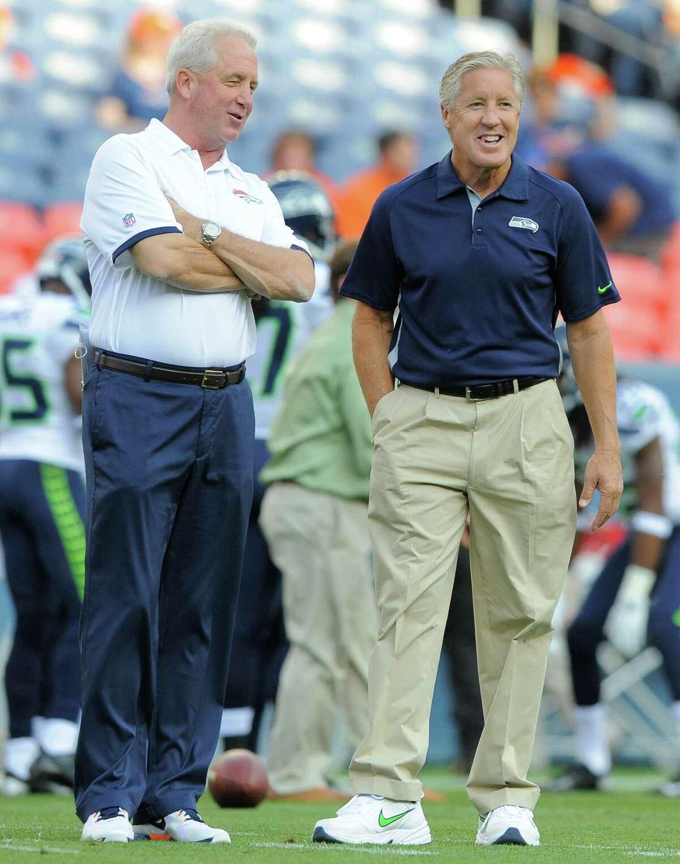 Denver Broncos head coach John Fox, left, and Seattle Seahawks head coach Pete Carroll, right, talk on the field.