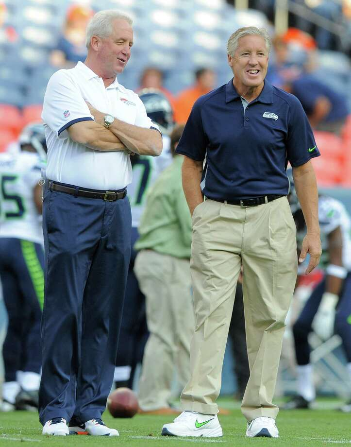 Denver Broncos head coach John Fox, left, and Seattle Seahawks head coach Pete Carroll, right, talk on the field. Photo: AP