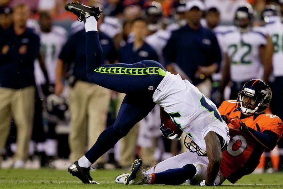 Running back Leon Washington #33 of the Seattle Seahawks is tackled by safety Mike Adams #20 of the Denver Broncos after a run for a gain of 12 yards during the second quarter. Photo: Justin Edmonds, Getty Images / 2012 Getty Images