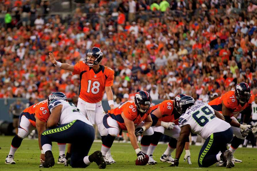 Quarterback Peyton Manning #18 of the Denver Broncos signals from the shotgun during the first quart