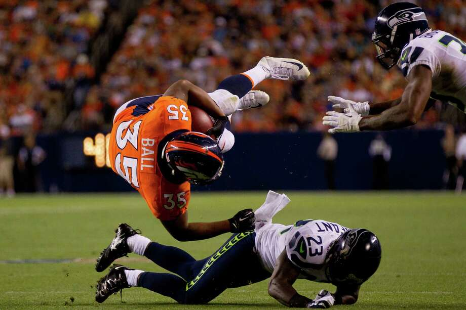Running back Lance Ball #35 of the Denver Broncos is upended by cornerback Marcus Trufant #23 of the Seattle Seahawks during the second quarter. Photo: Justin Edmonds, Getty Images / 2012 Getty Images