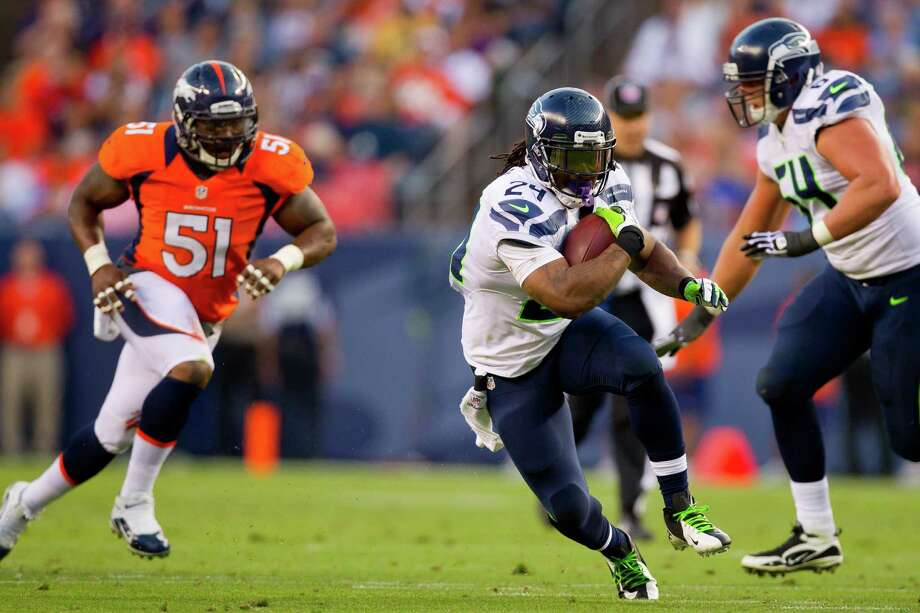 Running back Marshawn Lynch #24 of the Seattle Seahawks runs through a hole for a first down as linebacker Joe Mays #51 of the Denver Broncos gives chase and offensive guard J.R. Sweezy #64 looks to make a block during the first quarter. Photo: Justin Edmonds, Getty Images / 2012 Getty Images