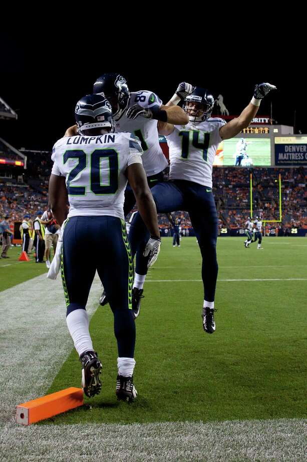 Cooper Helfet #84 of the Seattle Seahawks celebrates his 9 yard touchdown reception with teammates running back Kregg Lumpkin #20 and wide receiver Charly Martin #14 during the fourth quarter against the Denver Broncos. The Seahawks defeated the Broncos 30-10. Photo: Justin Edmonds, Getty Images / 2012 Getty Images
