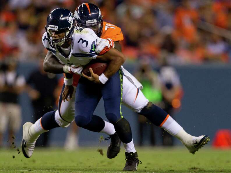 Quarterback Russell Wilson #3 of the Seattle Seahawks is sacked for a loss by defensive end Malik Ja