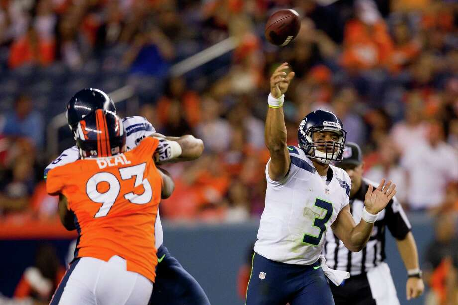 Quarterback Russell Wilson #3 of the Seattle Seahawks throws a pass for a completion as defensive end Jeremy Beal #93 of the Denver Broncos applies pressure during the fourth quarter. The Seahawks defeated the Broncos 30-10. Photo: Justin Edmonds, Getty Images / 2012 Getty Images