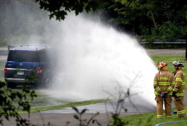 Firefighters use water from a fire house to disperse propane gas leaking from a filler pipe at Bryan Memorial Town Hall in Washington that was ruptured when a caterer drove a car across the lawn while cleaning up after a wedding Sunday Aug. 19, 2012.. Photo: John Pirro