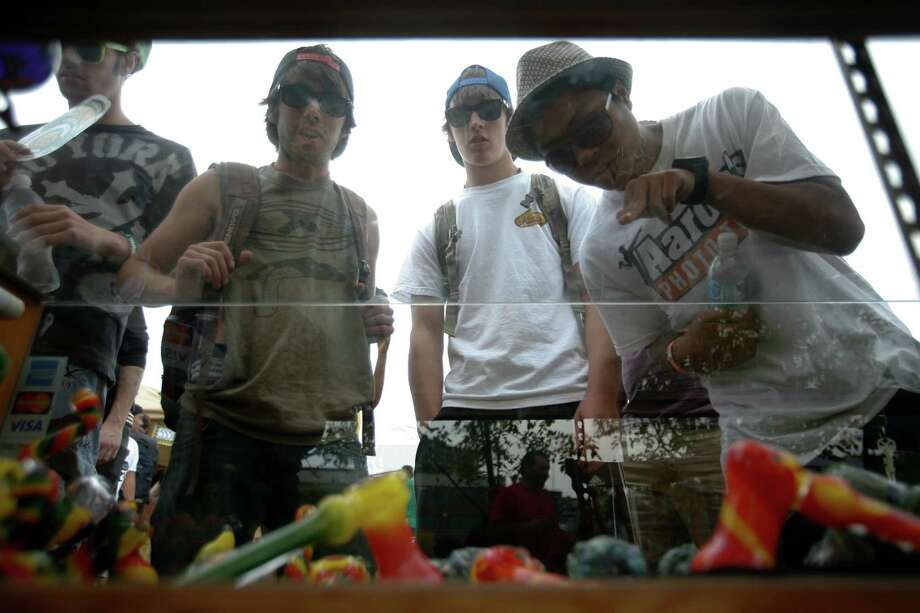 A group of men look through a glass dispay at a booth. Photo: Sofia Jaramillo / SEATTLEPI.COM