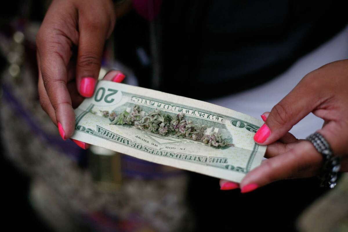 Marijuana is shown on a twenty dollar bill during day two of Seattle's Hempfest pro-marijuana gathering at Myrtle Edwards Park on the Seattle waterfront on Saturday, Aug. 18, 2012. Hundreds of thousands of people are expected to attend the festival that lasts through Sunday.