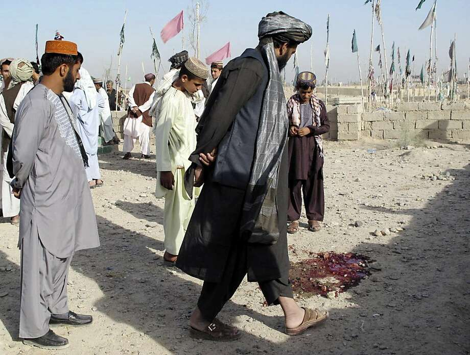 Afghans encounter a pool of blood on the way to a cemetery in Lashkar Gah in Afghanistan's Helmand province after a roadside bomb killed three relatives of the Nawa district police chief. Photo: Abdul Khaleq, Associated Press