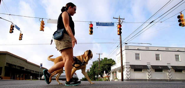 Guide dog trainer Natalie Garza of Guide Dogs of Texas walks with Alice the yellow lab  through the Monte Vita area Thursday August 16, 2012. Garza, whose husband is blind, trains working dogs for those in need. Photo: John Davenport, San Antonio Express-News / John Davenport/©San Antonio Exp
