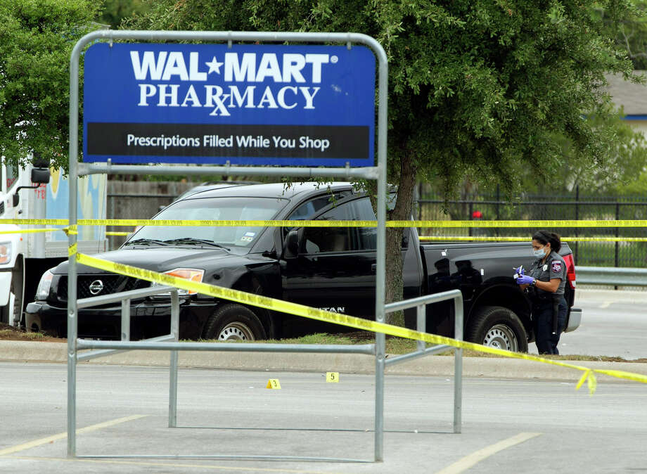 19 AUGUST 2012:  Cedar Park law enforcement investigate the scene of an early morning shooting in the parking lot of the Wal-Mart Super Center in Cedar Park, Texas, on Sunday, Aug. 19, 2012. Police say a suspect is in custody after four people were shot during an altercation in the Central Texas Walmart parking lot. (AP Photo/Austin American-Statesman, Rodolfo Gonzalez) Photo: Rodolfo Gonzalez, Associated Press / Austin American-Statesman