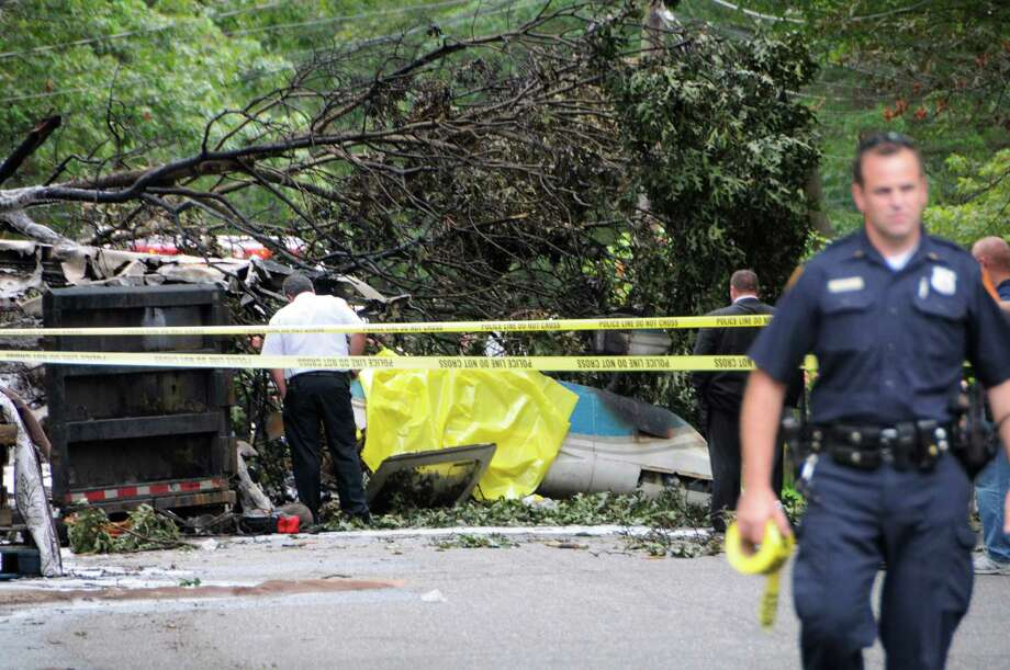 Authorities investigate the scene where a small plane carrying three people plummeted into a residential Long Island street in Shirley, N.Y.,  Sunday, Aug 19, 2012. The fiery crash killed one person aboard as neighbors tried to douse the flames with fire extinguishers and garden hoses. The single-engine, propeller plane went down around noon, shortly after taking off from nearby Brookhaven Calabro Airport, a Federal Aviation Administration spokeswoman said. (AP Photo/Newsday, John Roca)  NYC LOCALS OUT Photo: John Roca, Associated Press / Newsday