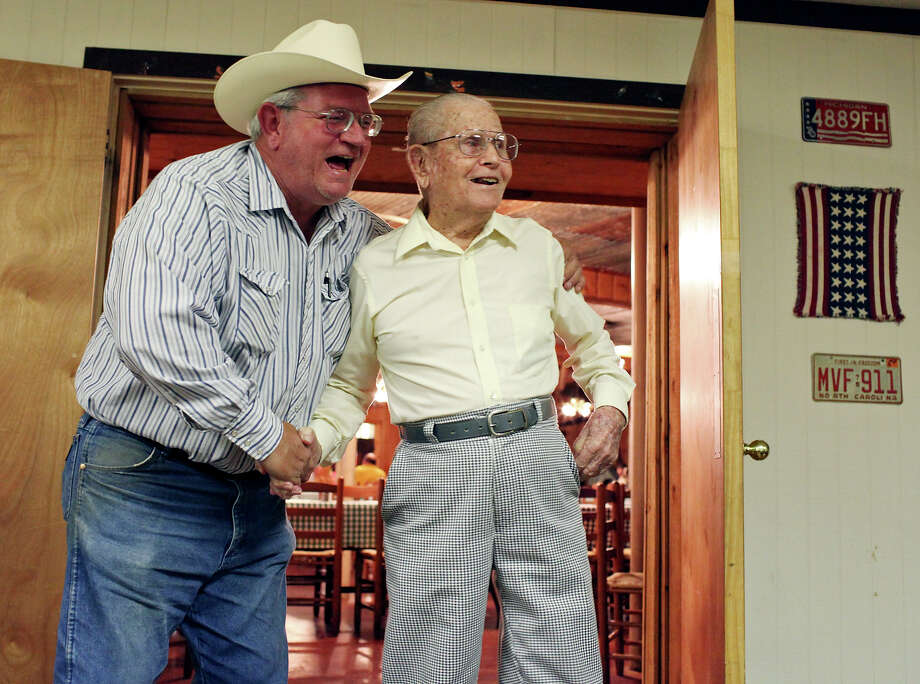 Milton Willmann, 56, shakes hands and wraps his arm around his uncle, retired Army Master Sgt. Henry Willmann, who will turn 95 on Aug. 27, as he enters his surprise early birthday party at Grady's Bar-B-Q 68 years after storming Normandy. Photo: Edward A. Ornelas, San Antonio Express-News / © 2012 San Antonio Express-News