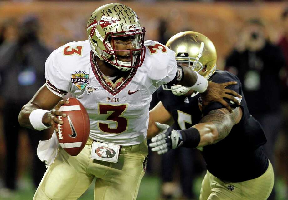 Florida State quarterback EJ Manuel (3) scrambles as he is pressured by Notre Dame linebacker Manti Te'o (5) during the first half of the Champs Sports Bowl NCAA college football game, Dec. 29, 2011, in Orlando, Fla. (AP Photo/John Raoux) Photo: John Raoux, Associated Press / AP