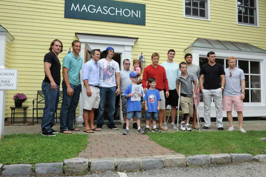 From left: Sean Backman, Bridgeport Sound Tigers; Nick Bonino, New York  Islanders; Martin St. Louis, Tampa Bay Lighting; Matt Moulson, New York  Islanders; Anthony Resta with Vincent, 8, Madelyne, 4, and Joseph, 6; Cam Atkinson, of the Columbus Blue Jackets; Chris Kreider, New York Rangers; Phil Desimone, Albany Devils; Danny New, Springfield Falcons; and another hockey professional. Photo: Helen Neafsey / Greenwich Time