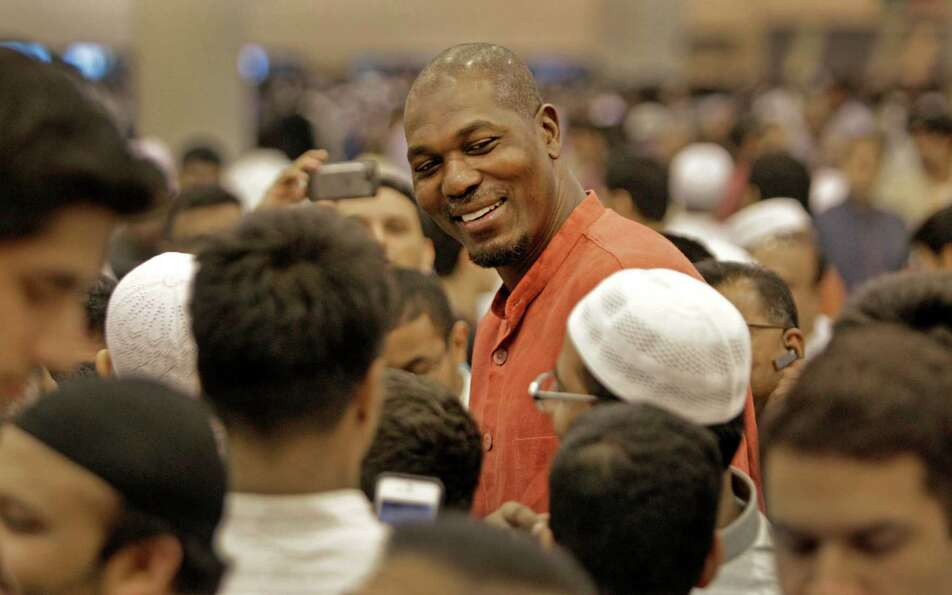 Former Houston Rockets player Hakeem Olajuwon is surrounded by crowd after an Eid prayer event hoste