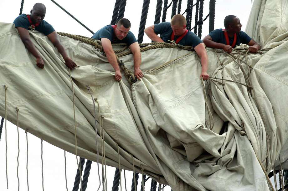 U.S. Navy personnel gather sails in the rigging of the USS Constitution as the vessel arrives at her berth in Charlestown Navy Yard, in Boston, Sunday, Aug. 19, 2012. The U.S. Navy's oldest commissioned war ship sailed under her own power Sunday for the first time since 1997. The sail was held to commemorate the 200th anniversary of the ship's victory over HMS Guerriere in the War of 1812. (AP Photo/Steven Senne) Photo: Steven Senne, Associated Press / AP