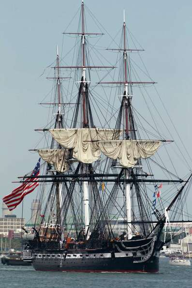 The USS Constitution is escorted by a tugboat in Boston Harbor in Boston, Sunday, Aug. 19, 2012. The