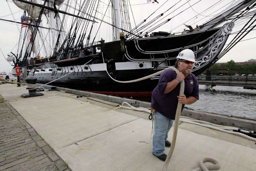 USS Constitution maintenance and repair crew member Michael Desmond, of Lynn, Mass., front, secures