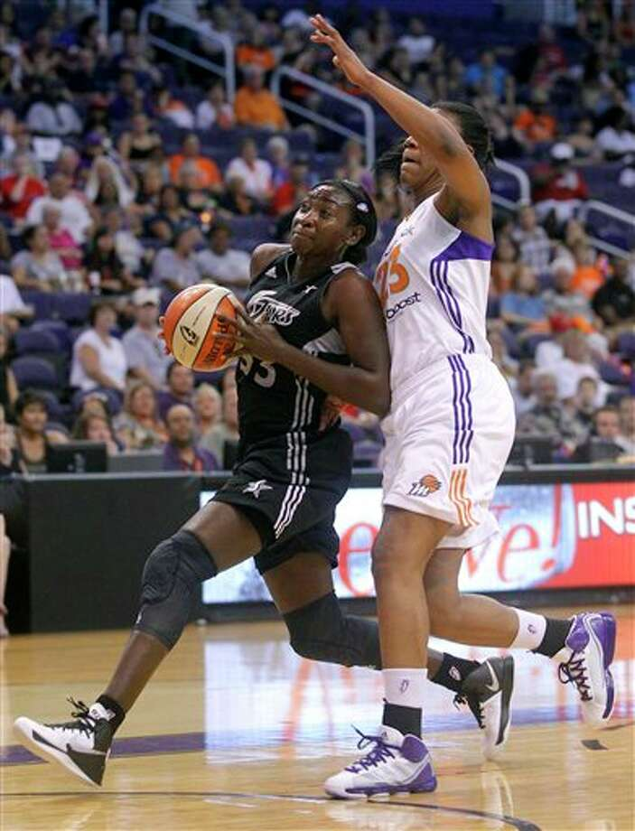 San Antonio Silver Stars forward Sophia Young, left, drives past Phoenix Mercury center Avery Warley during the first half of a WNBA basketball game on Sunday, Aug. 19, 2012, in Phoenix. (AP Photo/Matt York) Photo: Associated Press