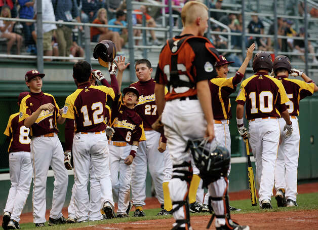 San Antonio McAllister Park players congratulate Jordan Cardenas, (12) after hitting a two-run homerun as New Castle, Indiana catcher Hunter McCubbins looks on during the sixth inning at the 2012 Little League World Series in South Williamsport, Pennsylvania, Sunday, Aug. 19, 2012. San Antonio won 13-3. The homerun also allowed Grant Gomez, (10), to score. Photo: Jerry Lara, Express-News / © 2012 San Antonio Express-News