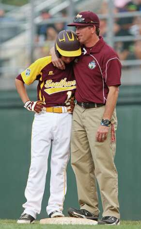 San Antonio McAllister Park Coach Kyle Elliott hugs Grant Gomez during break as New Castle, Indiana changes pitchers in the bottom of the fourth at the 2012 Little League World Series in South Williamsport, Pennsylvania, Sunday, Aug. 19, 2012. San Antonio won 13-3. Photo: Jerry Lara, Express-News / © 2012 San Antonio Express-News