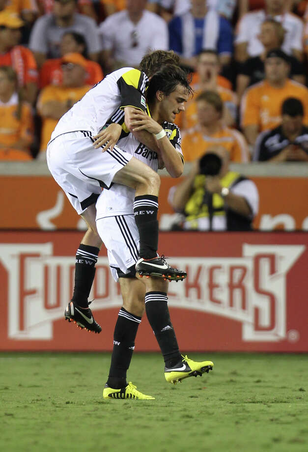 Columbus Crew's Eddie Gaven (12) jumps on his teammate Cole Grossman (22) after Grossman scored a goal during the first half of an MLS soccer game against the Houston Dynamo, Sunday, Aug. 19, 2012, in Houston. (AP Photo/Houston Chronicle, Karen Warren) Photo: Karen Warren, Associated Press / Houston Chronicle