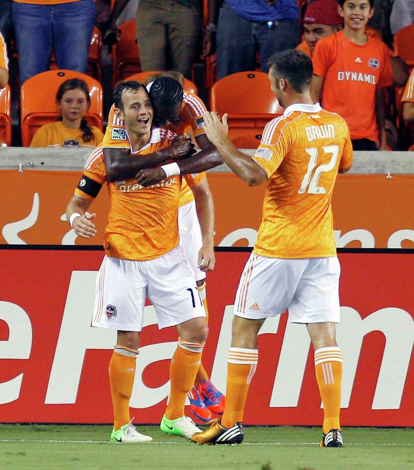 Brad Davis, left, celebrates with Dynamo teammates Macoumba Kandji, back, and Will Bruin after scoring on a shot inside the box. Photo: Bob Levey, Getty Images / 2012 Getty Images