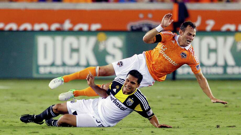 HOUSTON, TX - AUGUST 19:  Brad Davis #11 of the Houston Dynamo is tripped up by Jairo Arrieta #25 of the Columbus Crew in the first half at BBVA Compass Stadium on August 19, 2012 in Houston, Texas. Photo: Bob Levey, Getty Images / 2012 Getty Images