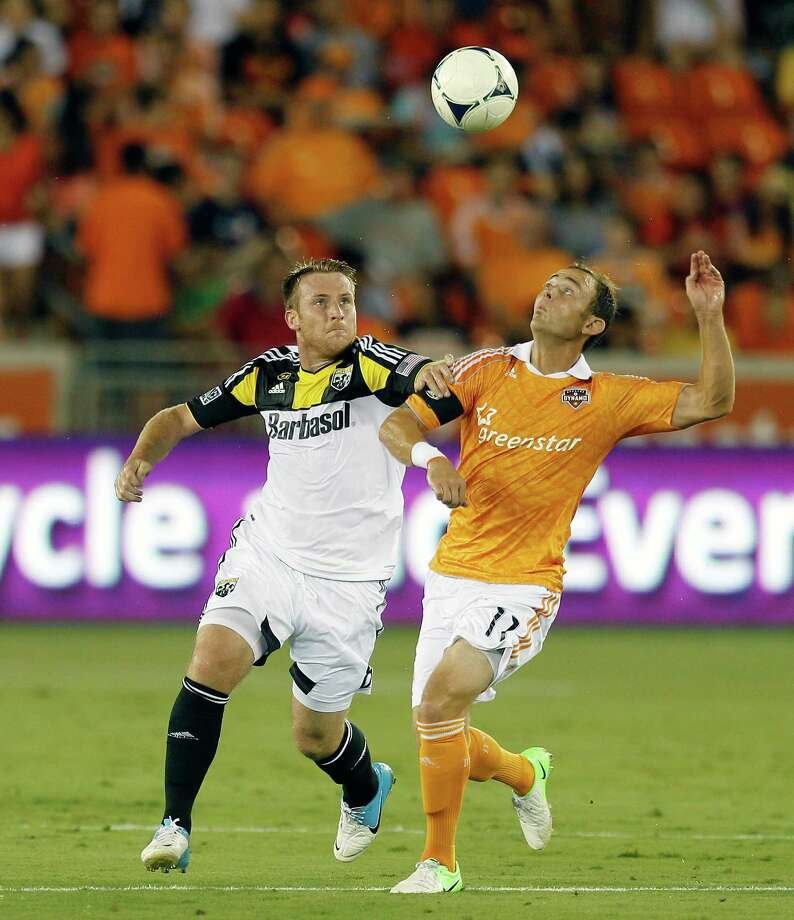 HOUSTON, TX - AUGUST 19:  Brad Davis #11 of the Houston Dynamo and Chris Birchall #8 of the Columbus Crew battle for possession of the ball in the first half  at BBVA Compass Stadium on August 19, 2012 in Houston, Texas. Photo: Bob Levey, Getty Images / 2012 Getty Images