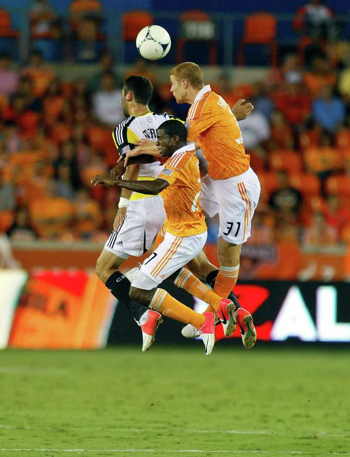 HOUSTON, TX - AUGUST 19:  Andre Hainault #31 of the Houston Dynamo goes up over Boniek Garcia #27 of the Houston Dynamo and Justin Meram #9 of the Columbus Crew for a header at BBVA Compass Stadium on August 19, 2012 in Houston, Texas. Photo: Bob Levey, Getty Images / 2012 Getty Images