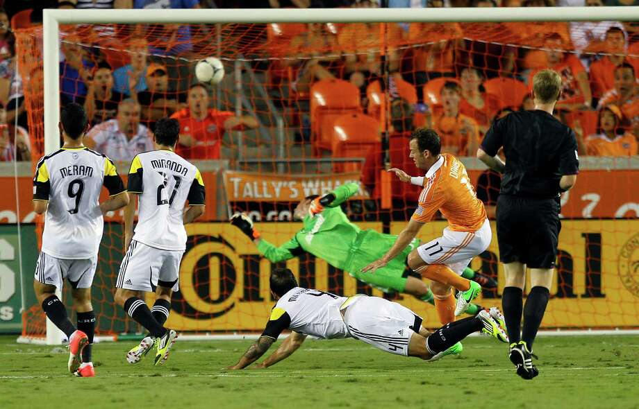 HOUSTON, TX - AUGUST 19: Brad Davis #11 of the Houston Dynamo stumbles over Carlos Mendes #4 of the Columbus Crew after scoring past a diving goalkeeper Andy Gruenebaum #30 of the Columbus Crew in the first half at BBVA Compass Stadium on August 19, 2012 in Houston, Texas. Photo: Bob Levey, Getty Images / 2012 Getty Images