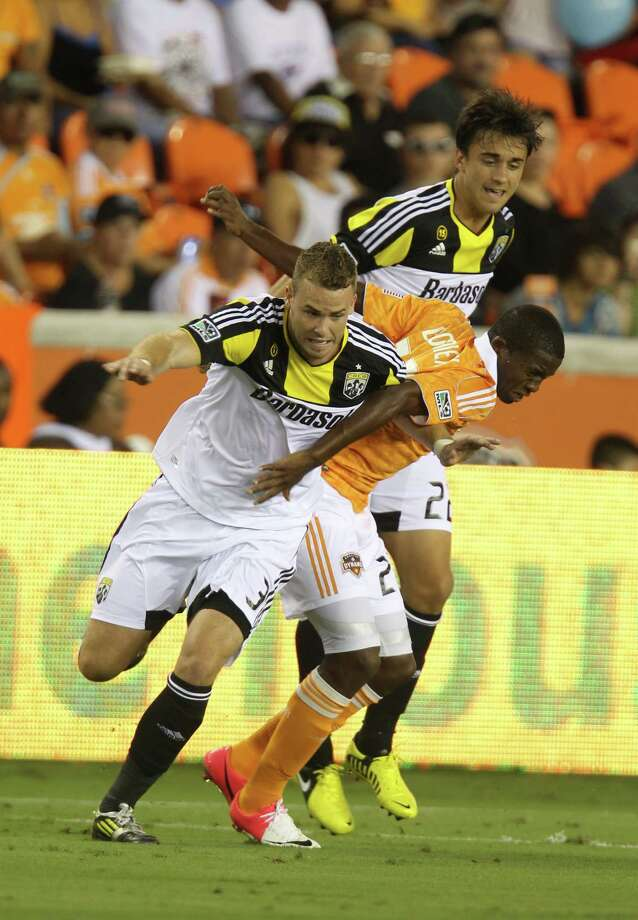 Houston Dynamo midfielder Boniek Garcia (27) is sandwiched by Columbus Crew midfielder Cole Grossman (22) and Columbus Crew defender Josh Williams (3) during the first half of an MLS soccer game at BBVA Compass Stadium, Sunday, Aug. 19, 2012, in Houston. Photo: Karen Warren, Houston Chronicle / © 2012  Houston Chronicle