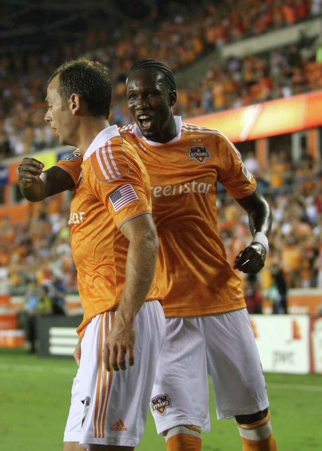 Houston Dynamo midfielder/forward Macoumba Kandji (9) screams as he goes to hug teammate Houston Dynamo midfielder Brad Davis (11) after Davis' goal during the first half of an MLS soccer game at BBVA Compass Stadium, Sunday, Aug. 19, 2012, in Houston. Photo: Karen Warren, Houston Chronicle / © 2012  Houston Chronicle