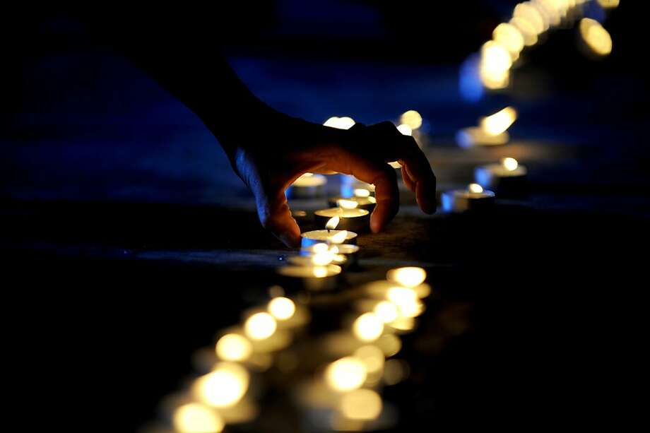 A college student lights candles during a ceremony to mark the 1,000th day since a 2009 massacre that left 57 people including journalists dead, in Manila on August 19, 2012. The protesters, who assembled at a human rights monument in Manila, also assailed President Benigno Aquino for the continued spate of killings of media workers despite his promises to crack down on such crimes.  TOPSHOTS AFP PHOTO/NOEL CELISNOEL CELIS/AFP/GettyImages Photo: Noel Celis, AFP/Getty Images