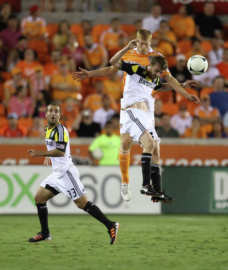 Houston Dynamo defender Andre Hainault (31) and Columbus Crew midfielder/forward Eddie Gaven (12) go up for a header during the second half of an MLS soccer game at BBVA Compass Stadium, Sunday, Aug. 19, 2012, in Houston. The game ended tied 2-2. Photo: Karen Warren, Houston Chronicle / © 2012  Houston Chronicle