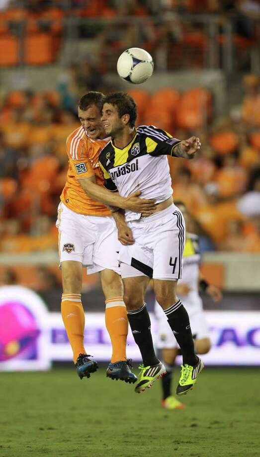 Houston Dynamo forward Cam Weaver (15) goes up against Columbus Crew defender Carlos Mendes (4) for the ball during the second half of an MLS soccer game at BBVA Compass Stadium, Sunday, Aug. 19, 2012, in Houston. The game ended tied 2-2. Photo: Karen Warren, Houston Chronicle / © 2012  Houston Chronicle