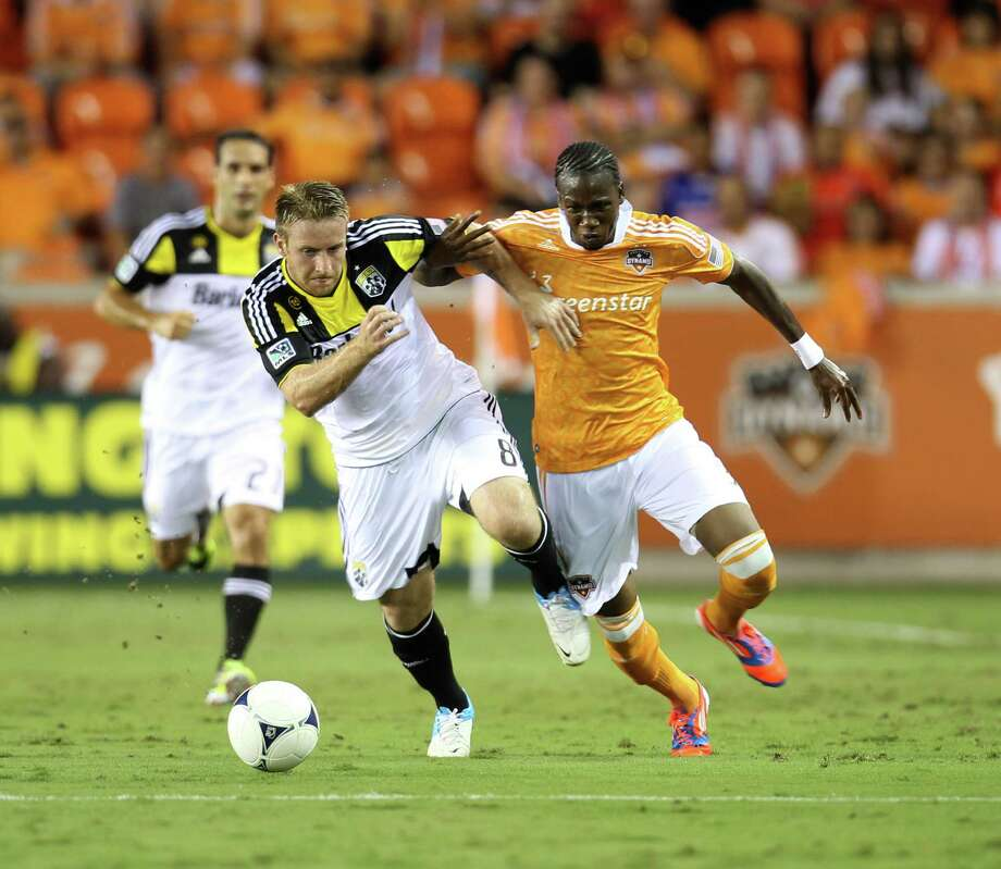 Columbus Crew midfielder Chris Birchall (8) and Houston Dynamo midfielder/forward Macoumba Kandji (9) battle for control of the ball during the first half of an MLS soccer game at BBVA Compass Stadium, Sunday, Aug. 19, 2012, in Houston. Photo: Karen Warren, Houston Chronicle / © 2012  Houston Chronicle
