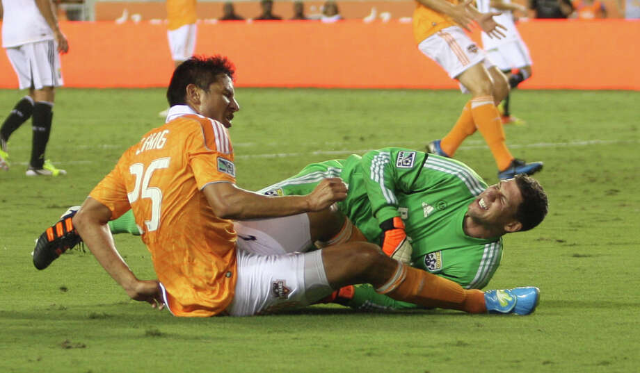 Houston Dynamo forward Brian Ching (25) collides with Columbus Crew goalkeeper Andy Gruenebaum (30) during the second half of an MLS soccer game at BBVA Compass Stadium, Sunday, Aug. 19, 2012, in Houston. The game ended tied 2-2. Photo: Karen Warren, Houston Chronicle / © 2012  Houston Chronicle