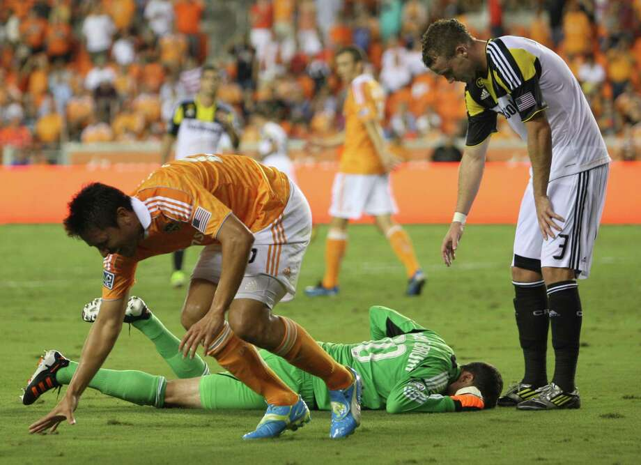 Houston Dynamo forward Brian Ching (25) reacts after colliding  with Columbus Crew goalkeeper Andy Gruenebaum (30) during the second half of an MLS soccer game at BBVA Compass Stadium, Sunday, Aug. 19, 2012, in Houston. The game ended tied 2-2. Photo: Karen Warren, Houston Chronicle / © 2012  Houston Chronicle