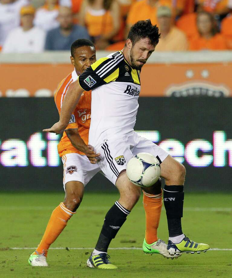 HOUSTON, TX - AUGUST 19:  Chris Birchall #8 of the Columbus Crew keeps the ball away from Ricardo Clark #13 of the Houston Dynamo in the second half at BBVA Compass Stadium on August 19, 2012 in Houston, Texas. Photo: Bob Levey, Getty Images / 2012 Getty Images
