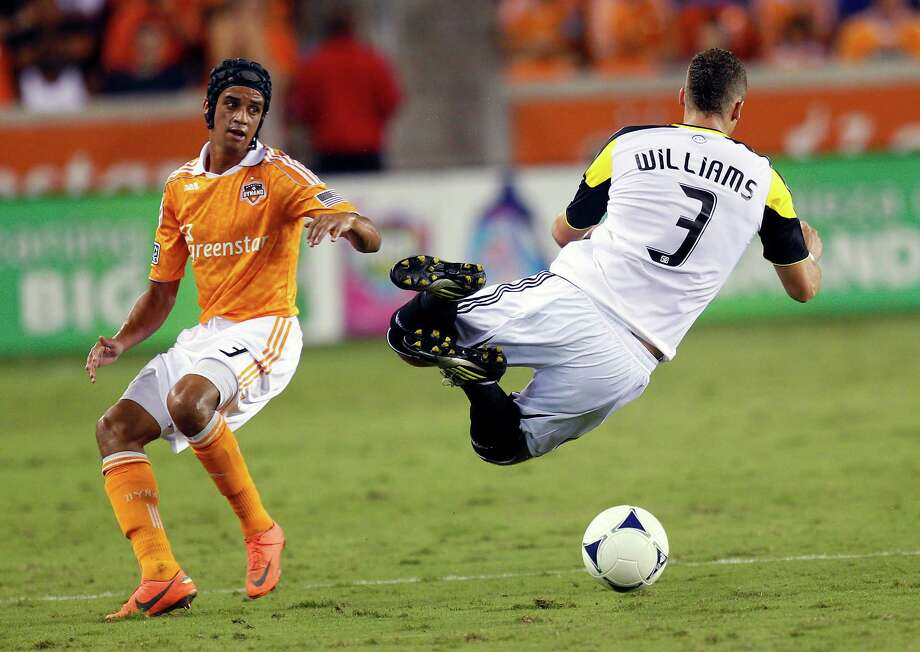 HOUSTON, TX - AUGUST 19:  Calen Carr #3 of the Houston Dynamo upends Josh Williams #3 of the Columbus Crew during the second half at BBVA Compass Stadium on August 19, 2012 in Houston, Texas. Photo: Bob Levey, Getty Images / 2012 Getty Images