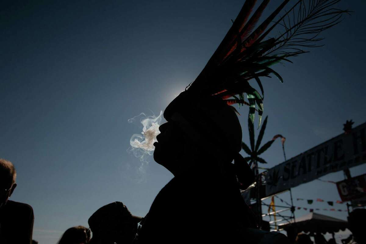 A man exhales smoke during the last day of Seattle's Hempfest at Myrtle Edwards Park on the Seattle waterfront on Sunday, Aug. 19, 2012.