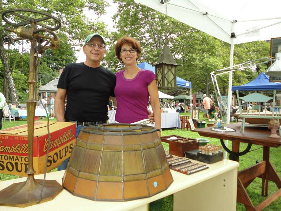 Richard and Debra Orsitti of D Lago Gallery of Torrington pose in their booth at the Westport Antiques & Vintage Market with a Tiffany lamp shade and a Green and Green outdoor hanging lantern Sunday. Photo: Meg Barone / Westport News freelance