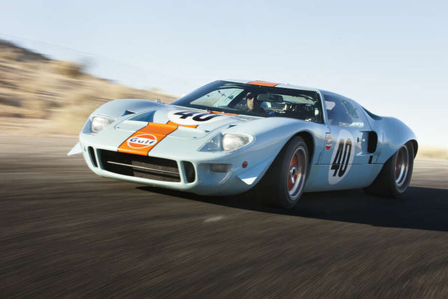 "A 1968 Ford GT40 racing car speeds down an open road. The car was used as a camera car for the 1971 Steve McQueen movie ""Le Mans."" It sold for $11 million. Photographer: Pawel Litwinski/RM Auctions via Bloomberg"